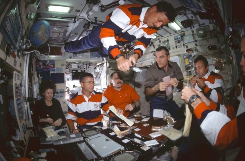 Moment de detente autour d'un repas dans le module de service pour célébrer le changement d'équipage